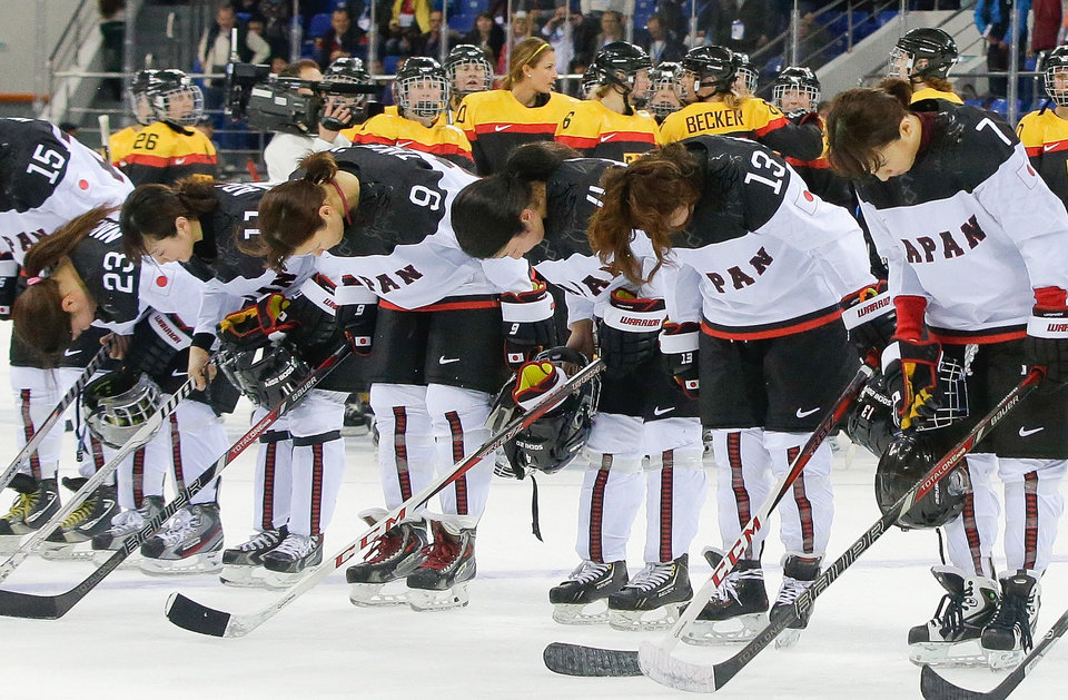 Photo - Members of team Japan bow after their 3-2 loss to Germany in the 2014 Winter Olympics women's ice hockey game at Shayba Arena, Tuesday, Feb. 18, 2014, in Sochi, Russia. (AP Photo/Matt Slocum)