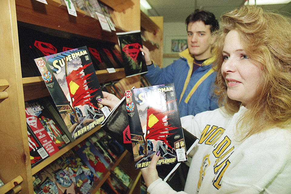 "Lori Horne of Boston grabs several copies of tthe ""Death of Superman"" comic book from the shelves of Comicopia in Boston during the first hours of sales Wednesday, Nov. 18, 1992. Chris Viveiros of Boston holds his copy of the comic book in the background. Another local store sold its entire supply of copies before noon. (AP Photo/Lisa Bull)"