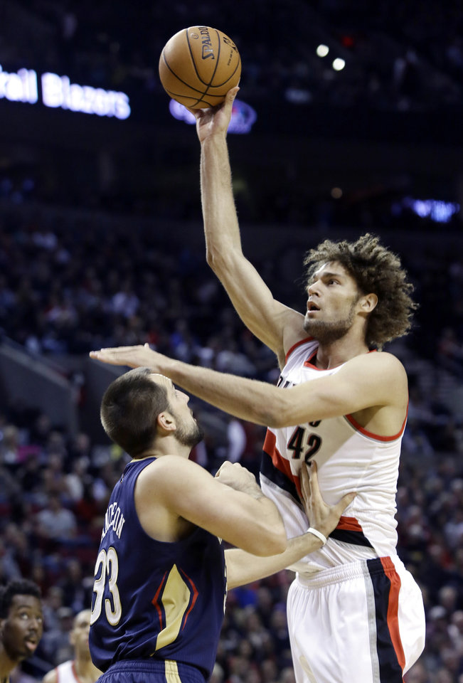 Photo - Portland Trail Blazers center Robin Lopez, right, shoots over New Orleans Pelicans forward Ryan Anderson during the first half of an NBA basketball game in Portland, Ore., Saturday, Dec. 21, 2013. (AP Photo/Don Ryan)