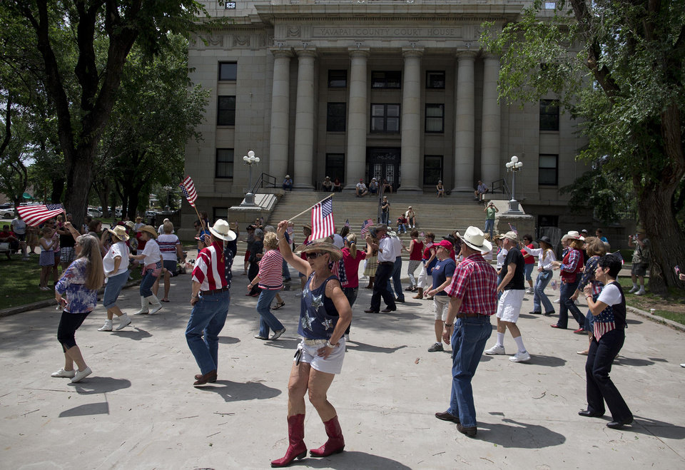 Visitors to the city square dance in a flash mob line dance with other Prescott city residents outside the Yavapai County Courthouse, Thursday, July 4, 2013 in Prescott, Ariz. After 19 Granite Mountain Hotshot firefighters were killed Sunday near Yarnell, Ariz., emotional whiplash has become a matter of course here as residents try to move on and enjoy the biggest tourism week of the year, while also mourning the men who were the town\'s pride. (AP Photo/Julie Jacobson)