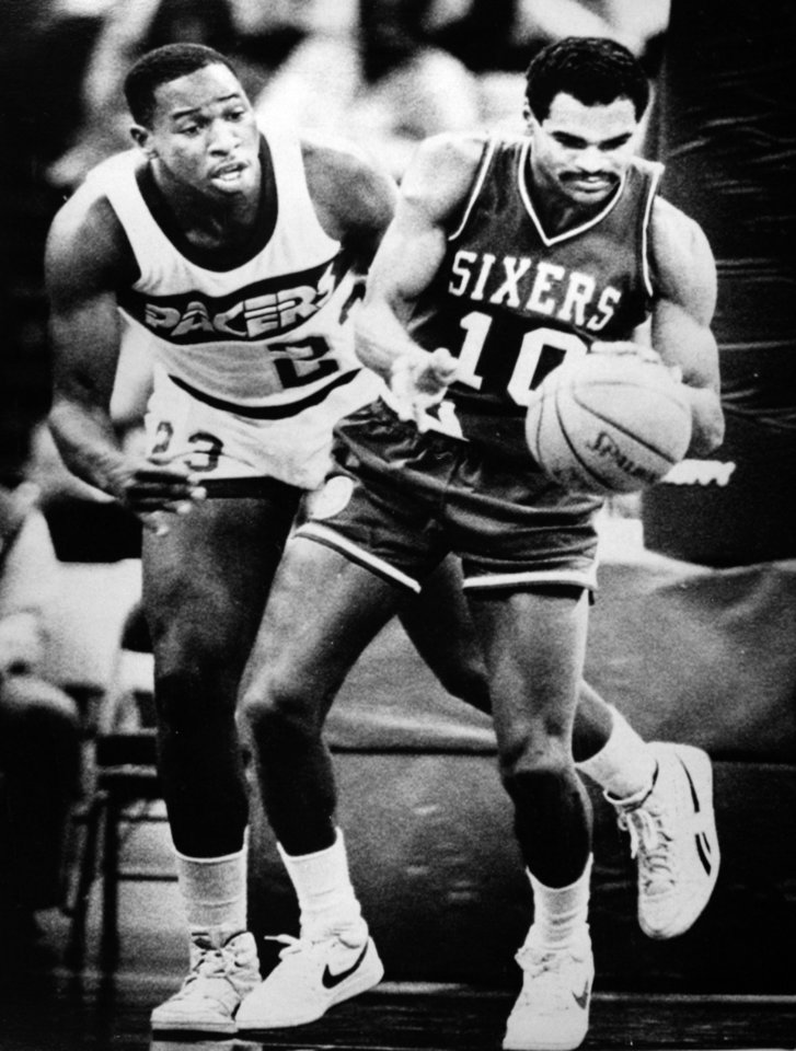 Former OU basketball player Wayman Tisdale. INDIANAPOLIS, Dec. 18 --SIXERS WIN-- Philadelphia 76er Maurice Cheeks, right, tries to control the ball as Indiana Pacer Wayman Tisdale, left, looks on in NBA action in Indianapolis Tuesday. The Sixers defeated the Pacers 102-96. (AP Laserphoto)  Photo by Michael Conroy. Photo taken 12/18/1985, photo published 3/23/1986 in The Daily Oklahoman. ORG XMIT: KOD