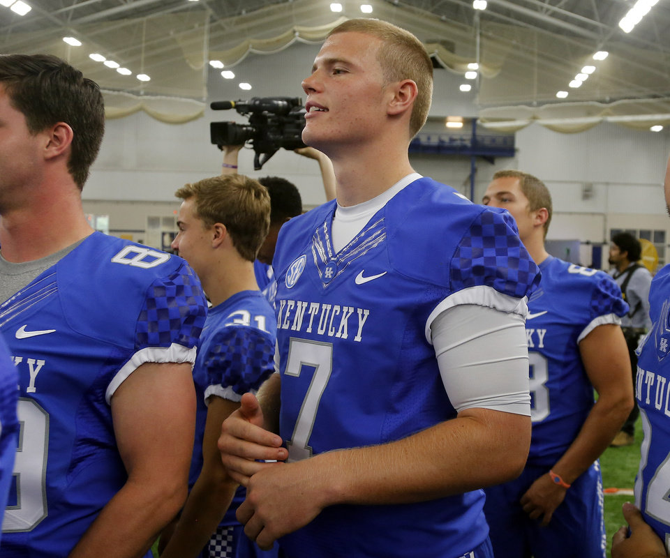 Photo - Kentucky's Drew Barker (7) watches as teammates are photographed during the team's NCAA college football media day, Friday, Aug. 8, 2014, in Lexington, Ky. (AP Photo/James Crisp)