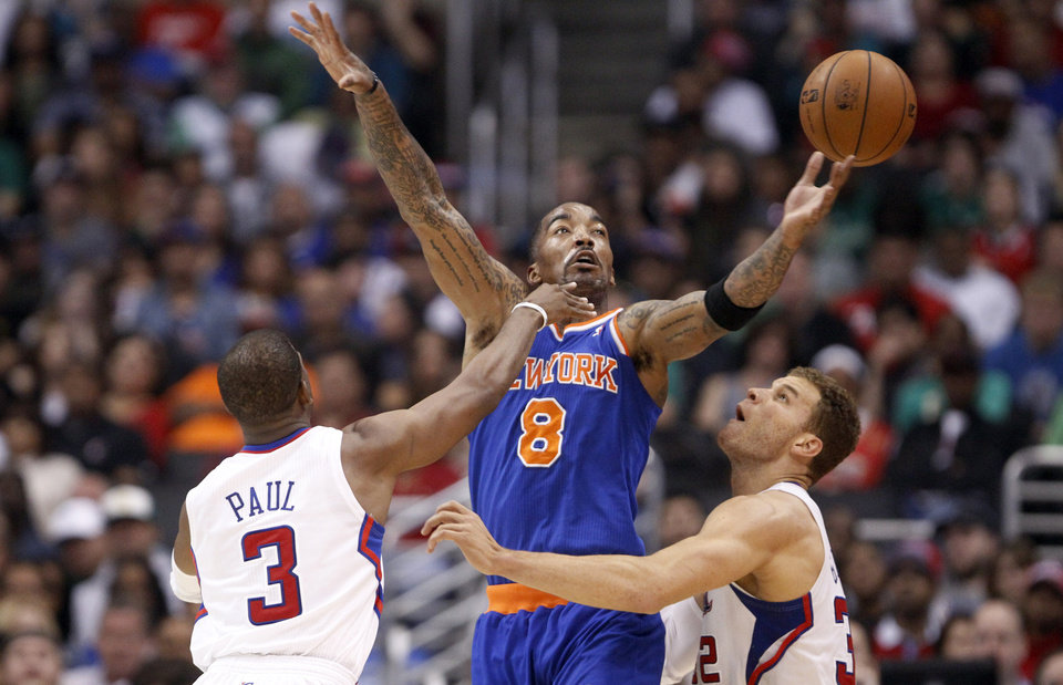 New York Knicks forward J.R. Smith (8) battles with Los Angeles Clippers guard Chris Paul (3) and orward Blake Griffin (32) in the first half of an NBA basketball game in Los Angeles Sunday, March 17, 2013. (AP Photo/Reed Saxon)