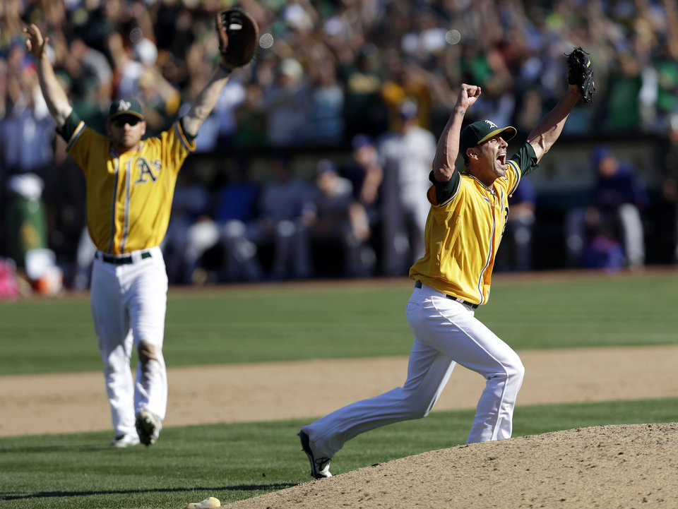 Photo -   Oakland Athletics relief pitcher Grant Balfour, right, celebrates the last out in their 12-5 win over the Texas Rangers in a baseball game, Wednesday, Oct. 3, 2012 in Oakland, Calif. The A's clinch the AL West title with the win. (AP Photo/Marcio Jose Sanchez)