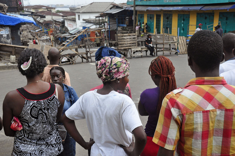 Photo - Residents from an area close to the West Point Ebola center, gather as they are not allowed to enter the area leading to their homes, after Liberia security forces blocked roads, as the government clamps down on the movement of people to prevent the spread of the Ebola virus in the city of Monrovia, Liberia, Wednesday, Aug. 20, 2014. Security forces deployed Wednesday to enforce a quarantine around a slum in the Liberian capital, stepping up the government's fight to stop the spread of Ebola and unnerving residents. (AP Photo/Abbas Dulleh)