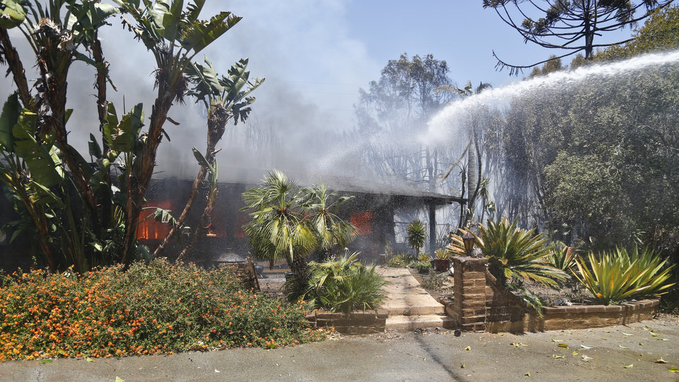 Photo - A home is fully engulfed in flames as a wildfire burns Wednesday, May 14, 2014, in Carlsbad, Calif. Carlsbad city officials said mandatory evacuations were in progress Wednesday, and more than 11,000 notices were sent to homes and businesses. (AP Photo)