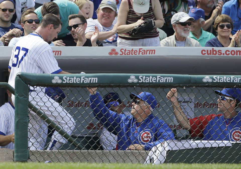 Photo - Chicago Cubs' Travis Wood, left, celebrates with manager Rick Renteria after scoring on a single hit by Javier Baez during the fifth inning of an interleague baseball game against the Tampa Bay Rays in Chicago, Sunday, Aug. 10, 2014. (AP Photo/Nam Y. Huh)