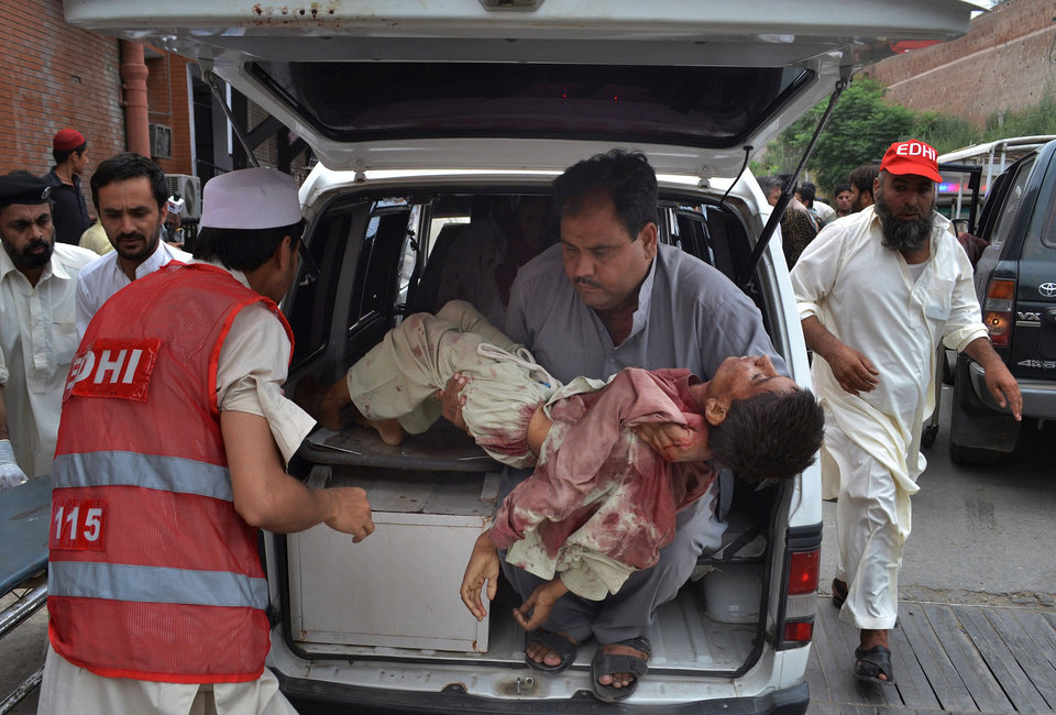 Photo - A Pakistani carries a critically injured boy, a victim of a car bombing, from an ambulance upon his arrival at a local hospital in Peshawar, Pakistan, Sunday, June 2013. A car bomb exploded as a convoy of paramilitary troops passed through the outskirts of the northwest Pakistani city of Peshawar, killing at least a dozen people and wounding scores of others, police said. (AP Photo/Hussain Ali)
