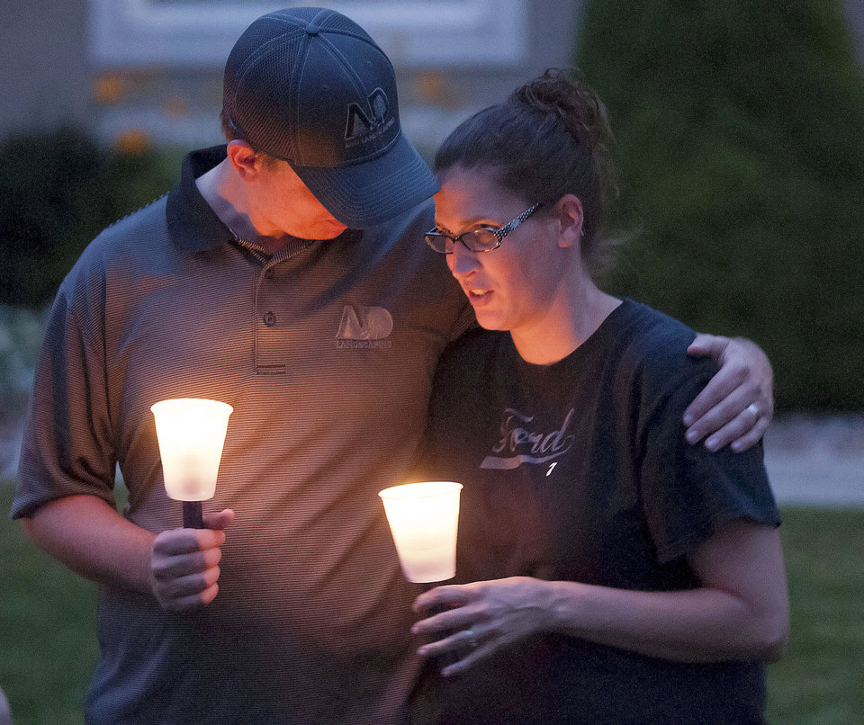 Photo - Steve and Cyndi Ford, who were friends of the Haskell family gather for a candlelight vigil, Thursday, July 10, 2014, in Logan, Utah. Ronald Lee Haskell and his family lived in Logan for several years. (AP Photo/The Herald Journal, Eli Lucero)