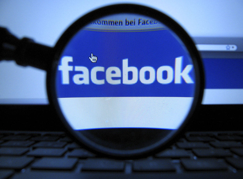 A magnifying glass is posed over a monitor on a Facebook page displayed in Munich, Germany. AP Photo