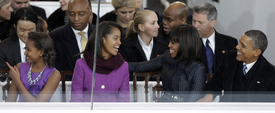 President Barack Obama, first lady Michelle Obama gesture with their daughters Malia, second from left, and Sasha, left, while sitting in the Presidential box on Pennsylvania Avenue in front of the White House Monday, Jan. 21, 2013, in Washington. Thousands marched during the 57th Presidential Inauguration parade after the ceremonial swearing-in of President Obama. (AP Photo/Gerald Herbert) ORG XMIT: DCMS142