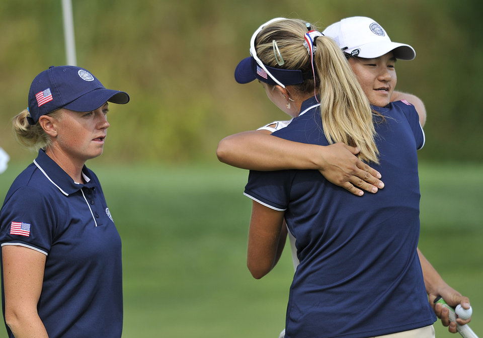 Photo - Yani Tseng, right, of Taiwan, is congratulated by Lexi Thompson, center, and Stacy Lewis after completing the first round of the International Crown golf tournament on Thursday, July 24, 2014, in Owings Mills, Md. (AP Photo/Gail Burton)