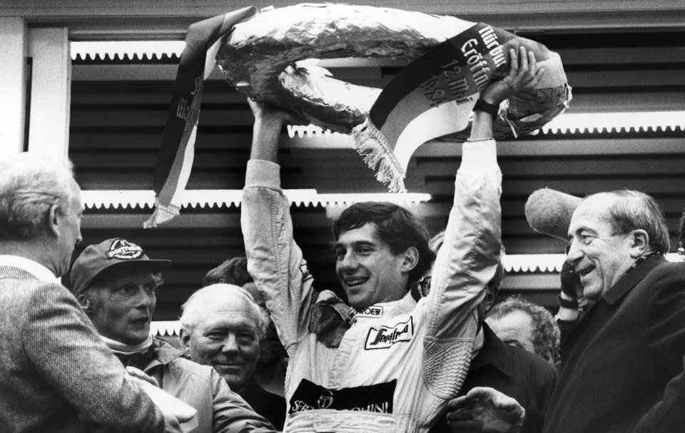 Photo - FILE - In this May 13, 1984, file photo, Brazilian Formula One race driver Ayrton Senna da Silva, center, holds up the winner's crown after he won the Mercedes 190 E race in Nuremberg, Germany  ahead of former world champion Niki Lauda, second from left. At the right, smiling German transport minister Werner Dollinger. Senna won three Formula One titles — in 1988, 1990 and '91 — all with McLaren. He moved to the Williams team for his tragic 1994 season. Despite his career being cut short when he was 34, his 41 wins stand third all-time behind Michael Schumacher's 91 and rival Alain Prost's 51. He died at the 1994 San Marino Grand Prix. (AP Photo/Udo Weitz, File)