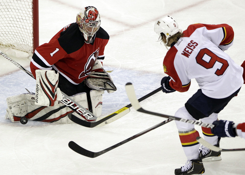 Photo -   New Jersey Devils' Johan Hedberg (1), of Sweden, makes a save on a shot by Florida Panthers' Stephen Weiss (9) during the third period of Game 3 of a first-round NHL hockey Stanley Cup playoff series, Tuesday, April 17, 2012, in Newark, N.J. The Panthers won 4-3. (AP Photo/Julio Cortez)
