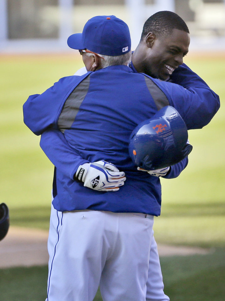 Photo - New York Mets' Curtis Granderson, right, hugs manager Terry Collins after hitting a walk-off sacrifice fly during the fourteenth inning of the baseball game at Citi Field, Sunday, April 20, 2014 in New York. The Mets defeated the Braves in extra innings 4-3. (AP Photo/Seth Wenig)