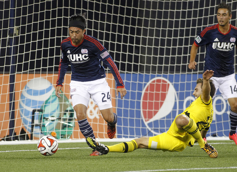 Photo - Columbus Crew's Chad Barson, right, attempts to kick a loose ball as New England Revolution's Lee Nguyen (24) prevents it from crossing the goal line during the second half of an MLS soccer game, Saturday, July 26, 2014, in Foxborough, Mass. Columbus defeated New England 2-1. (AP Photo/Stew Milne)