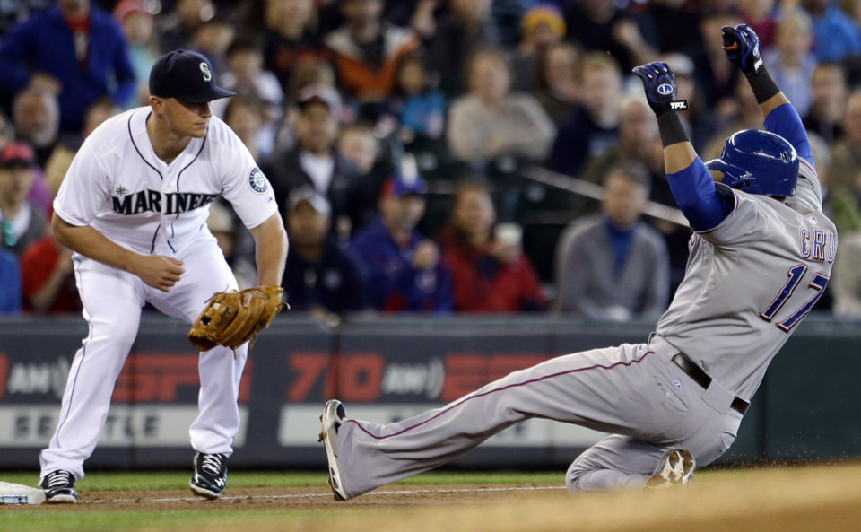 Texas Rangers' Nelson Cruz, right, slides into a tag by Seattle Mariners third baseman Kyle Seager while trying to stretch his double into a triple in the fourth inning in a baseball game on Sunday, May 26, 2013, in Seattle. (AP Photo/Elaine Thompson)