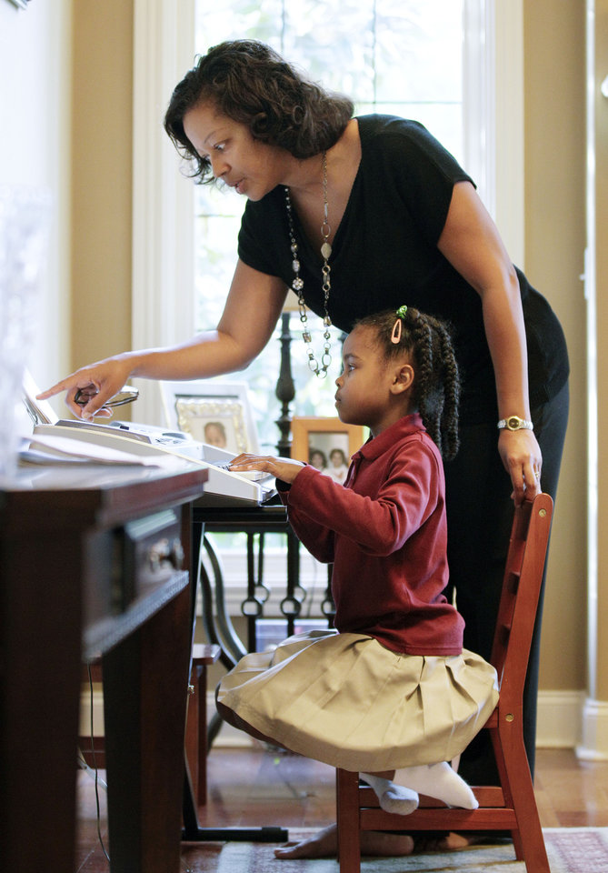 Photo -   In this April 17, 2012 photo, Dr. Christi Witherspoon helps her daughter, Rachel, 6, with a music lesson in Nashville, Tenn. Tennessee is one of only a few states that has passed laws creating evaluations or contracts that put helping with homework or attending teacher conferences into writing. (AP Photo/Mark Humphrey)