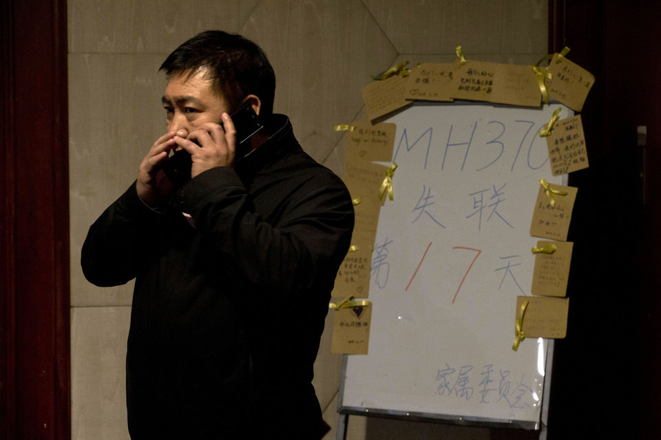 Photo - A man whispers on a cellphone near a board which reads