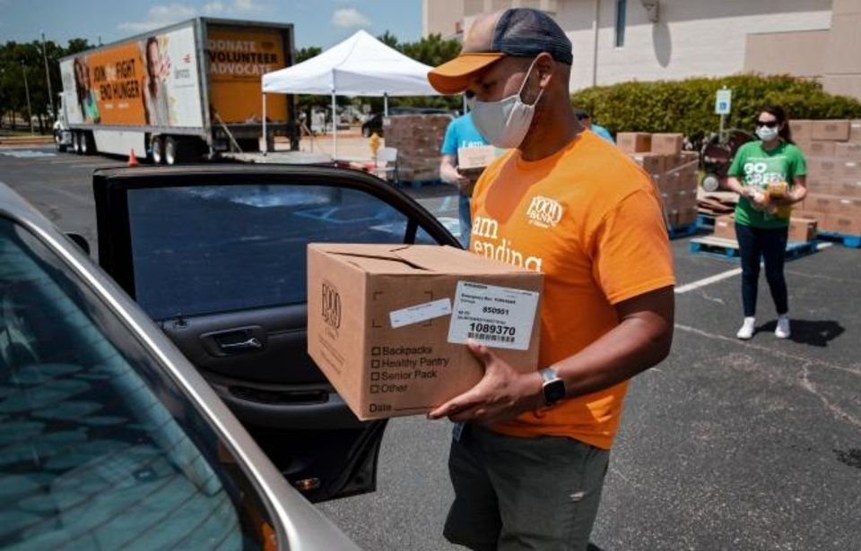 Photo -  John Bobb-Semple loads a box of food into a clients car during the Regional Food Bank of Oklahoma food distribution event for individuals seeking unemployment assistance on Wednesday, July 8, 2020, in Midwest City, Okla.  [Chris Landsberger/The Oklahoman]