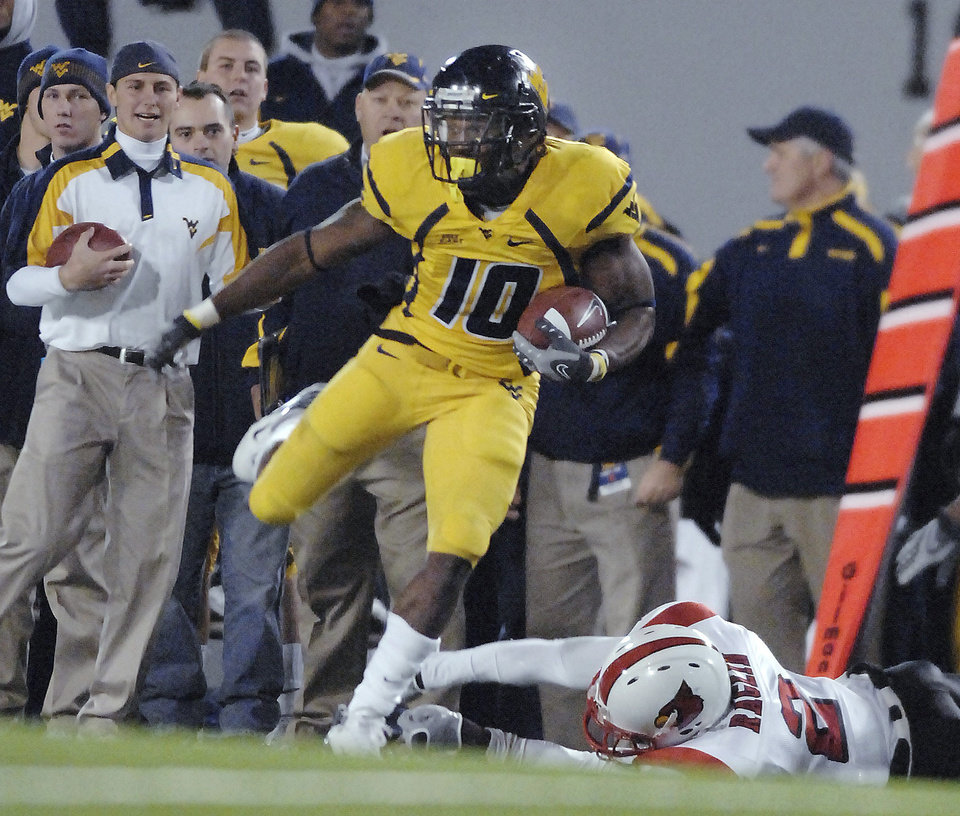 Photo - University of West Virginia's Steve Slaton (10) carries the ball past University of Louisville's Richard Raglin (2) during the first half of a college football game Thursday, Nov. 8, 2007, in Morgantown, W.Va. (AP Photo/Jeff Gentner) ORG XMIT: WVJG101