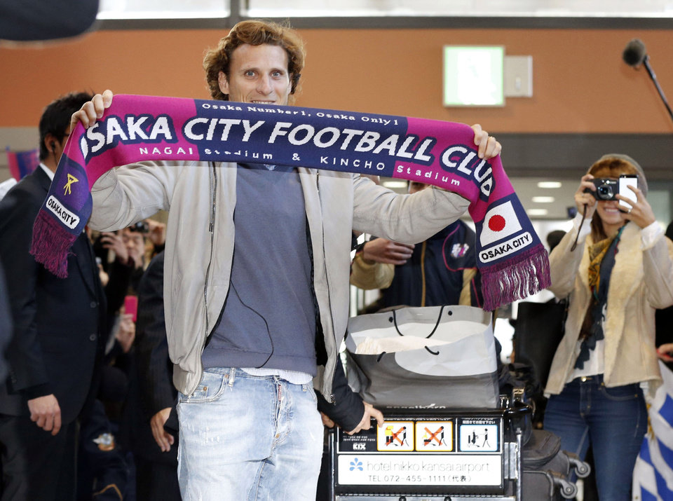 Photo - Uruguay striker Diego Forlan poses with a scarf on his arrival at Kansai International Airport in Osaka, western Japan Wednesday, Feb. 12, 2014. Forlan will play for Cerezo Osaka in Japan. (AP Photo/Kyodo News) JAPAN OUT, MANDATORY CREDIT