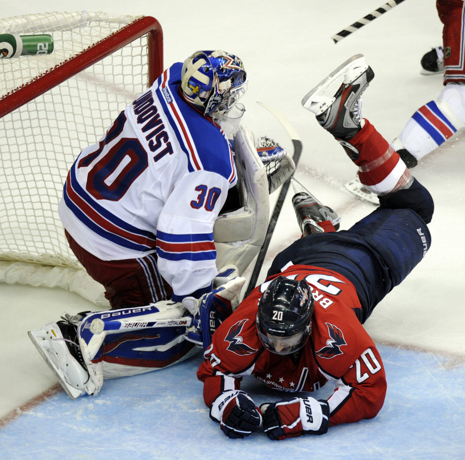 Photo -   Washington Capitals left wing Troy Brouwer (20) dives in front of New York Rangers goalie Henrik Lundqvist (30) during the second overtime period of Game 3 of their NHL hockey Stanley Cup second-round playoff series at the Verizon Center in Washington, Wednesday, May 2, 2012. (AP Photo/Susan Walsh)