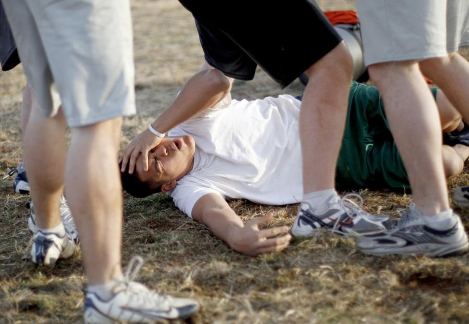 Photo -  Armando Matlala, 15, of Edmond Santa Fe holds his head after getting hit during an Edmond Rugby Club practice in Edmond, Okla., Tuesday, January 26, 2010.  Photo by Bryan Terry, The Oklahoman ORG XMIT: KOD