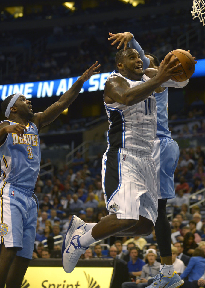 Orlando Magic center Glen Davis (11) goes up for a shot between Denver Nuggets guard Ty Lawson (3) and Andre Iguodala (obscured) during the first half of an NBA basketball game in Orlando, Fla., Friday, Nov. 2, 2012. (AP Photo/Phelan M. Ebenhack)