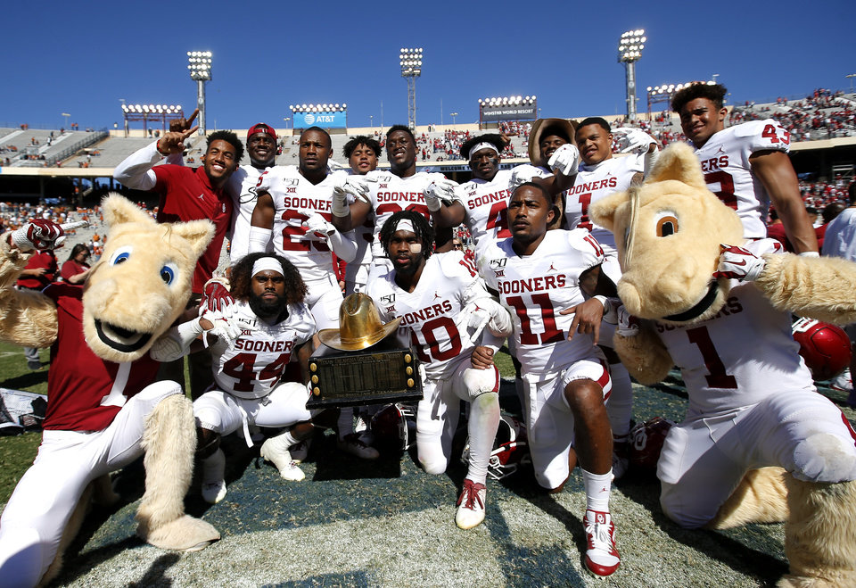 Photo - Oklahoma players celebrate with the Golden Hat Trophy during the Red River Showdown college football game between the University of Oklahoma Sooners (OU) and the Texas Longhorns (UT) at Cotton Bowl Stadium in Dallas, Saturday, Oct. 12, 2019. OU won 34-27. [Sarah Phipps/The Oklahoman]