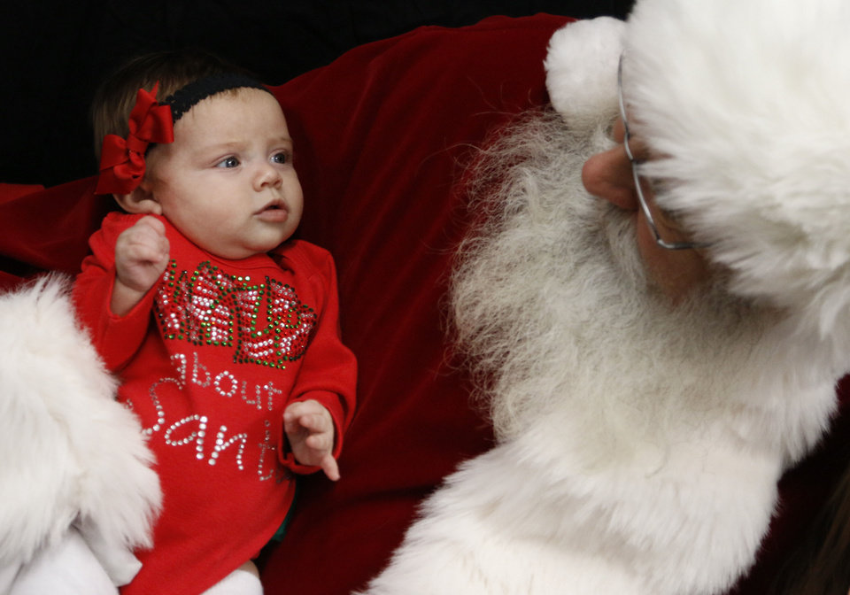 Photo - Payden Parish, 3 months old, checks out jolly old St. Nick at an Edmond Police Department holiday event.  Photo by Paul Hellstern, The Oklahoman  PAUL HELLSTERN - Oklahoman