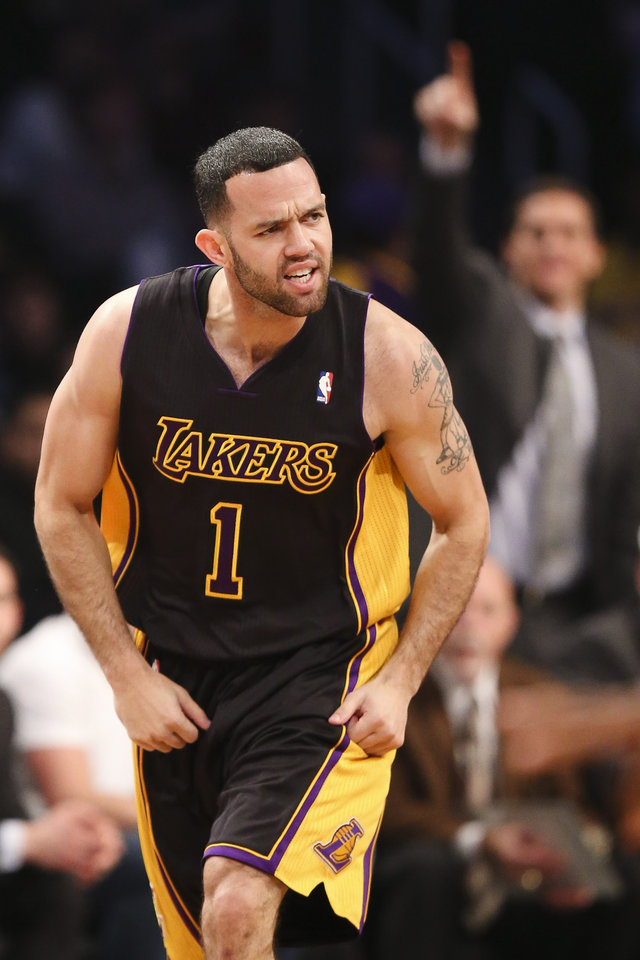 Photo - Los Angeles Lakers point guard Jordan Farmar (1) reacts after scoring three points on a stolen ball in the second quarter of an NBA basketball game against the Brooklyn Nets at the Barclays Center, Wednesday, Nov. 27, 2013, in New York. (AP Photo/John Minchillo)