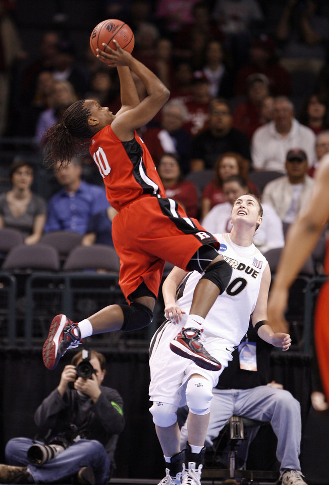 Photo - Epiphany Prince drives for a basket against Jodi Howell in the first half of the NCAA women's basketball tournament game between Rutgers and Purdue at the Ford Center in Oklahoma City, Okla. on Sunday, March 29, 2009. 