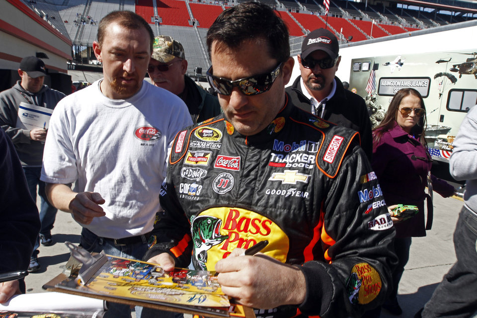 Photo - Driver Tony Stewart (14) signs autographs before practice for the NASCAR Sprint Cup series auto race at Bristol Motor Speedway on Friday, March 14, 2014, in Bristol, Tenn. (AP Photo/Wade Payne)