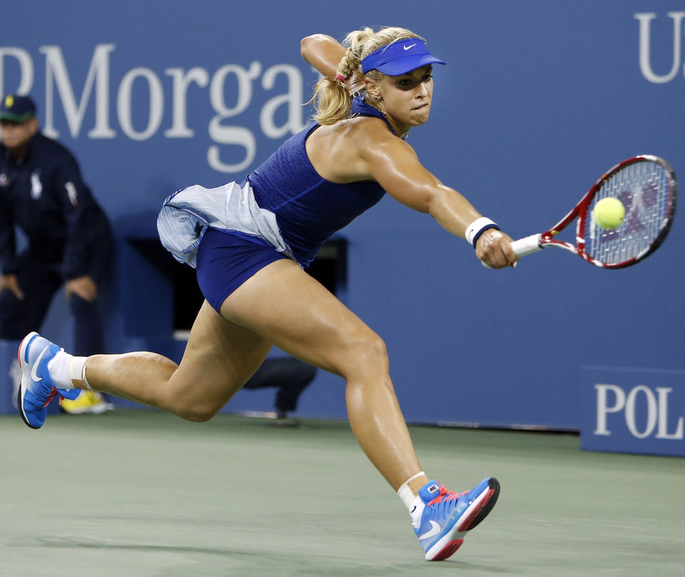 Photo - Sabine Lisicki, of Germany, stretches to return a shot to Maria Sharapova, of Russia, during the third round of the U.S. Open tennis tournament Friday, Aug. 29, 2014, in New York. (AP Photo/Jason DeCrow)