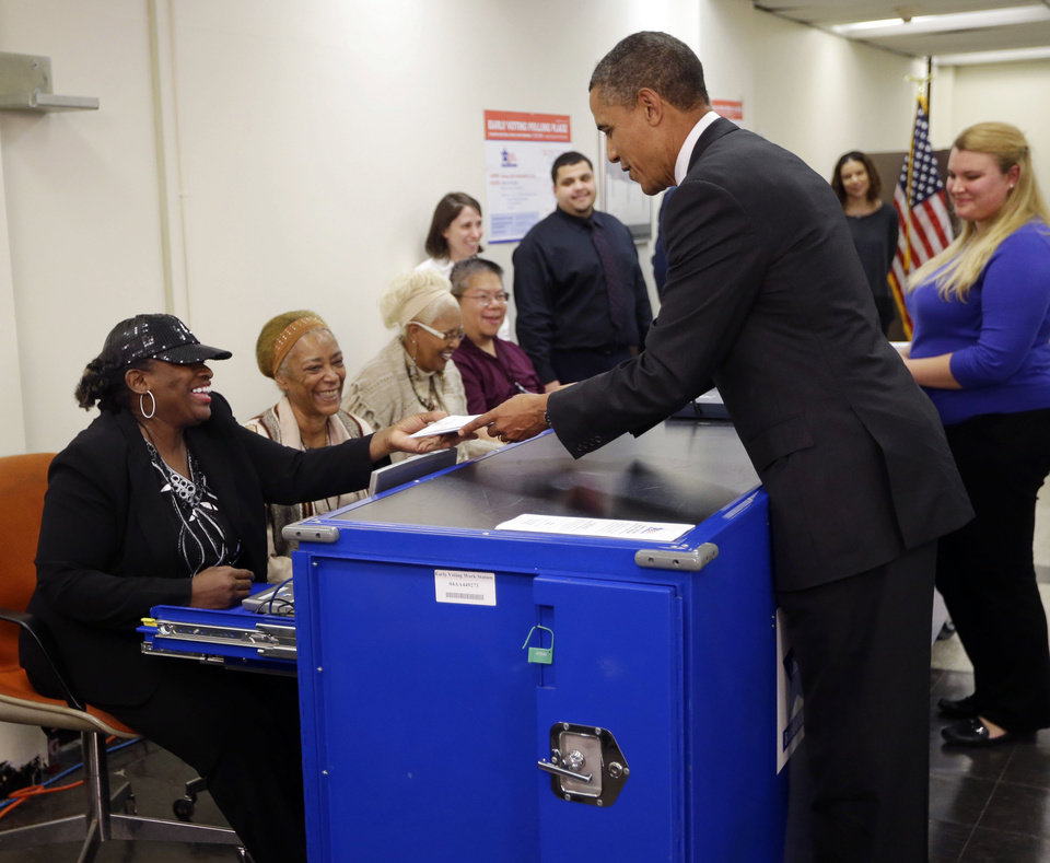 Photo -   President Barack Obama, right, turns in his ballot receipt to election official Marie Holmes, left, as he prepares to cast his vote, during early voting, in the 2012 election at the Martin Luther King Community Center, Thursday, Oct. 25, 2012, in Chicago. (AP Photo/Pablo Martinez Monsivais)