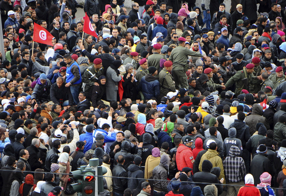 Photo - Thousands of Tunisians are gathered at el Jallez cemetery to attend the funerals of slain opposition leader Chokri Belaid, near Tunis, Friday Feb. 8, 2013. The Wednesday Feb. 6 assassination of prominent government critic Chokri Belaid plunged the country into one of its deepest political crises since the overthrow of the dictatorship in 2011. The coffin is carried by pallbearers at center of picture.(AP Photo/Hassene Dridi)