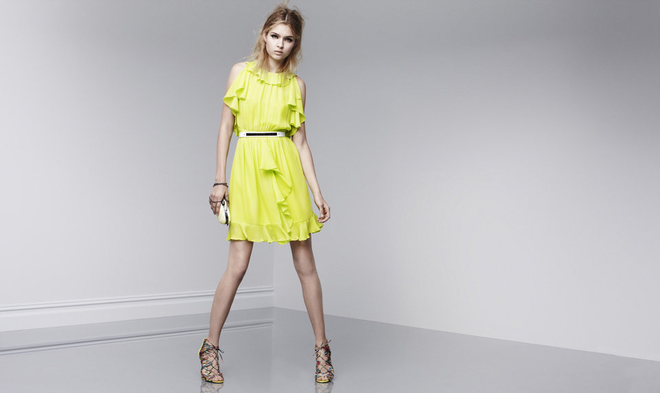 "One trick to ""dressing rich"" is to wear a ""statement"" dress, according to fashion expert Anna Johnson. Here is a bright lemon yellow ruffled dress with statement shoes from Prabal Gurung's new designer collection at Target, coming out Feb. 10."