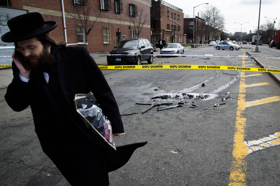 Photo - A man walks past debris from a fatal accident that claimed the lives of two expectant parents on their way to the hospital early, Sunday, March 3, 2013, in the Brooklyn borough of New York. A driver struck the car the couple were riding in early Sunday morning, killing both parents while their baby, who was born prematurely, survived and is in critical condition. (AP Photo/John Minchillo)