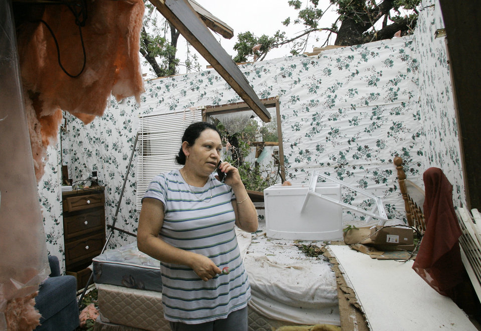 Photo - Yolanda Suarez talks on her cell phone in what is left of the bedroom of her mobile home Tuesday in Seminole. Several tornadoes swept through Oklahoma on Monday, leaving a path of destruction, including Suarezs home. AP Photo