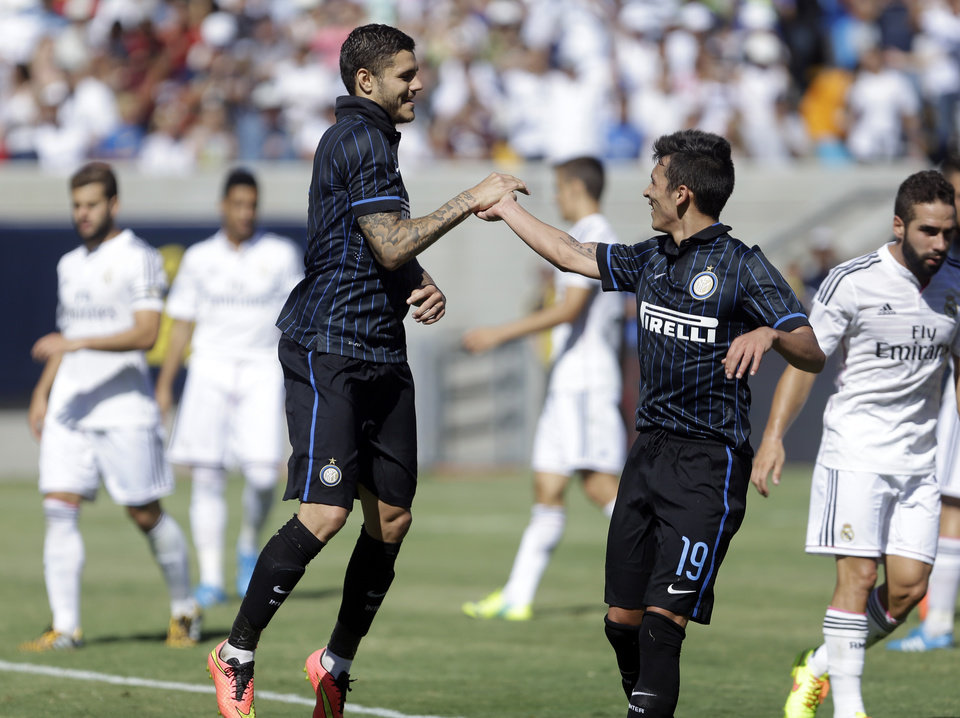Photo - Inter Milan's Mauro Icardi, left, is congratulated by Ruben Botta (19) after Icardi scored a goal against Real Madrid during the second half of a soccer match in the first round of the Guinness International Champions Cup, Saturday, July 26, 2014, in Berkeley, Calif. (AP Photo/Ben Margot)