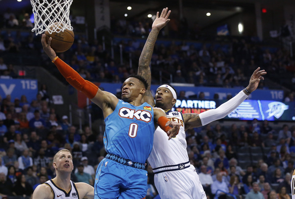 Photo - Oklahoma City Thunder guard Russell Westbrook (0) shoots in front of Denver Nuggets' Torrey Craig, right, and Mason Plumlee during the second half of an NBA basketball game Friday, March 29, 2019, in Oklahoma City. (AP Photo/Sue Ogrocki)
