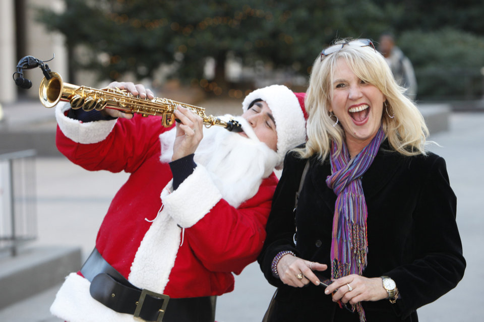 "Sax Playing Santa, Justin Young, plays to LeeAnn Moore outside Chase Tower, Monday, December 17, 2012.  This is an Arts Council Arts Moves event called Shade of Blue, ""A Charlie Brown Christmas""   Photo By David McDaniel/The Oklahoman"