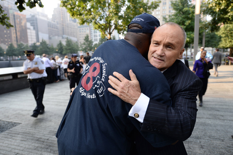Photo - New York City Police Commissioner Ray Kelly, right, hugs a friend at the 9/11 Memorial during ceremonies marking the 12th anniversary of the 9/11 attacks on the World Trade Center in New York, Wednesday, Sept. 11, 2013. (AP Photo/Stan Honda, Pool)