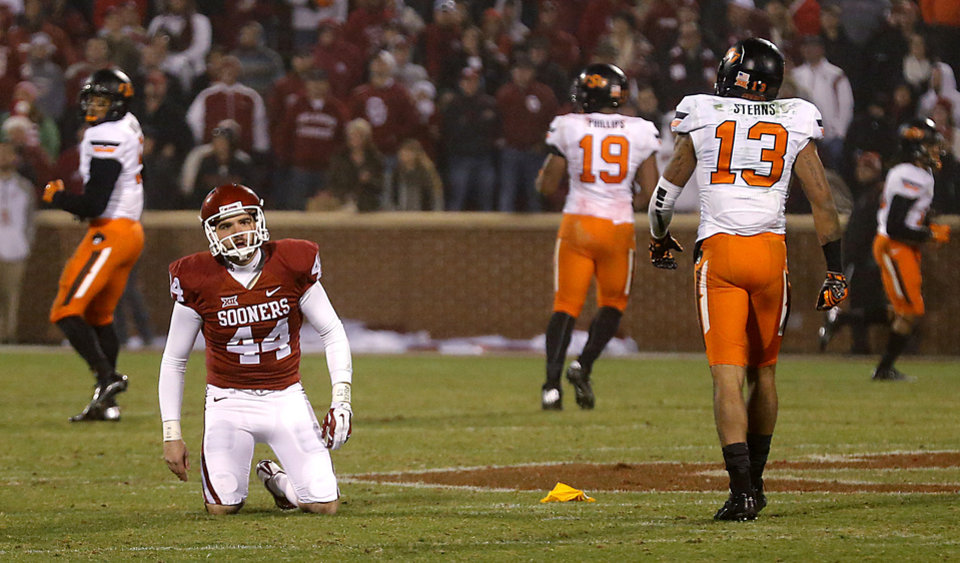 Photo - Oklahoma's Jed Barnett (44) gets up after being knocked down by Oklahoma State's Jordan Sterns (13) on a punt attempt during a Bedlam college football game between the University of Oklahoma Sooners (OU) and the Oklahoma State University Cowboys (OSU) at the Gaylord Family Oklahoma Memorial Stadium in Norman, Okla. on Saturday, Dec. 6, 2014. Photo by Chris Landsberger, The Oklahoman