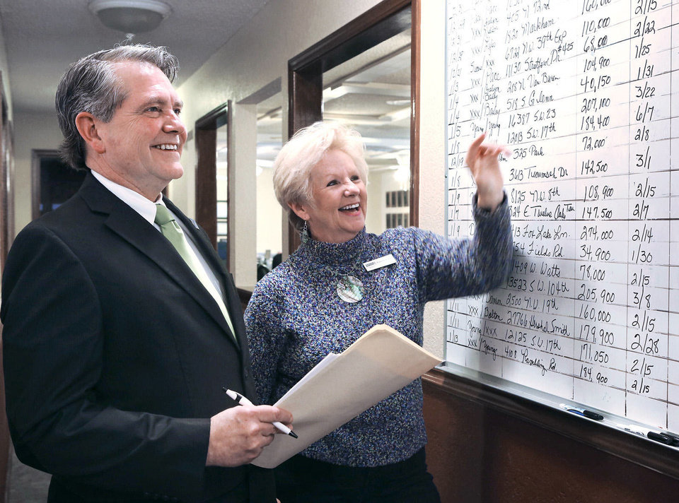 Realtors Keith Taggart and Paulette Statler look at a wallboard of listings at the Coldwell Banker Select office in Mustang. Taggart is 2013 president of the Oklahoma City Metro Association of Realtors.  Photos by Jim Beckel, THE OKLAHOMAN