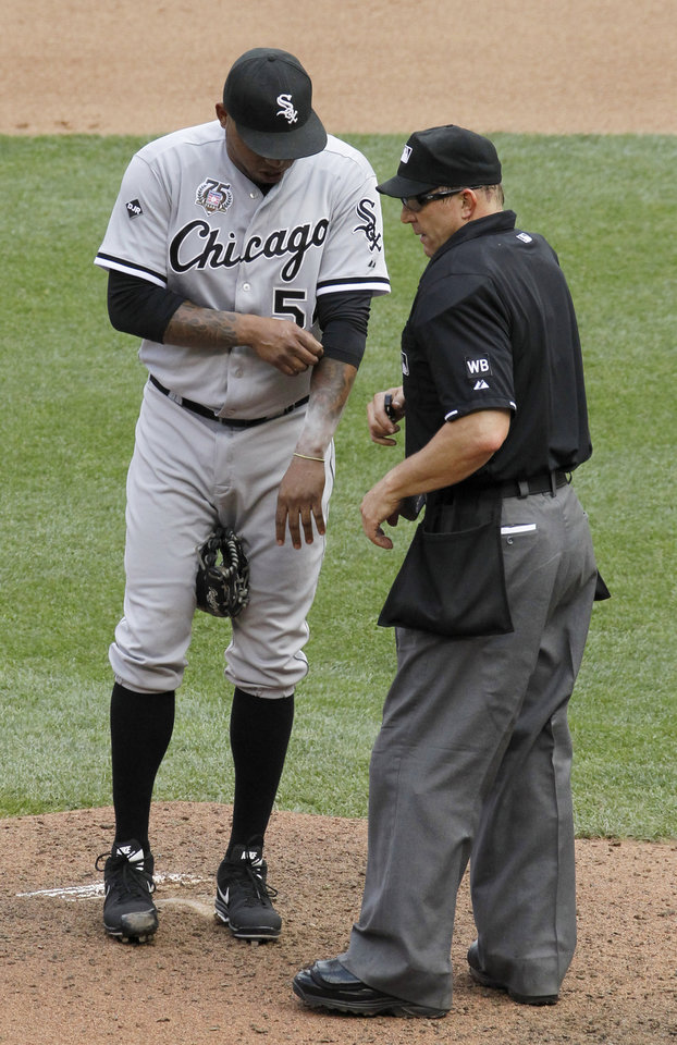 Photo - Home plate umpire Jeff Kellogg, right, checks a bracelet on the left arm of Chicago White Sox relief pitcher Ronald Belisario, left, before asking Belisario to remove it during the seventh inning of a baseball game in Minneapolis, Sunday, July 27, 2014. The Twins won 4-3. (AP Photo/Ann Heisenfelt)