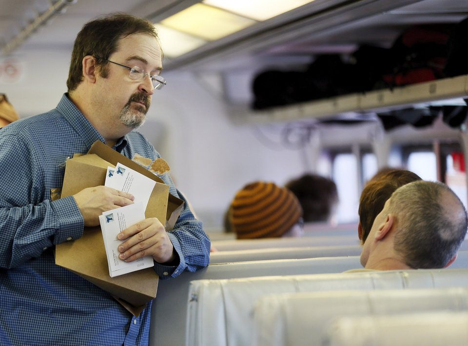 Photo - Evan Stair of Norman, Okla., with Passenger Rail Oklahoma passes out postcards to passengers to send to Gov. Mary Fallin encouraging her to keep the tracks that would be used by the Eastern Flyer state-owned, on a demonstration ride of the Eastern Flyer passenger train from Sapulpa to the Oklahoma City metro area, Sunday, Feb. 23, 2014. Photo by Nate Billings, The Oklahoman