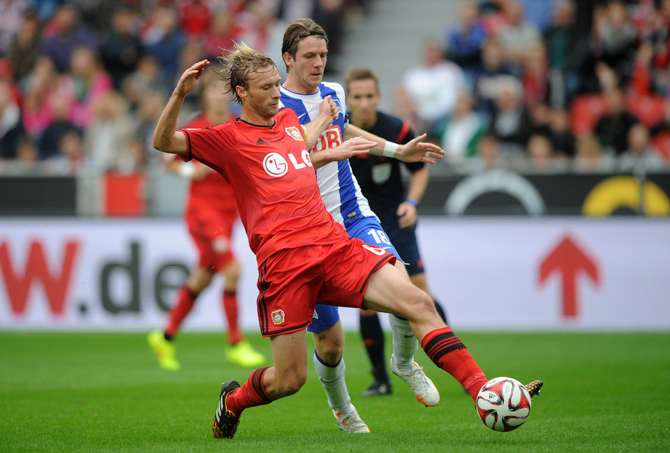 Photo - Leverkusen's Simon Rolfes, left, challenges for the ball with  Berlin's Peter Niemeyer during the German Bundesliga soccer match between Bayer Leverkusen and Hertha BSC Berlin in Leverkusen, western Germany, Saturday Aug. 30, 2014. (AP Photo/dpa,Jonas Guettler)
