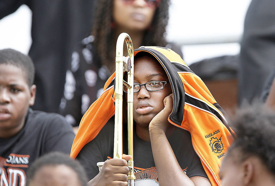 A member of the Douglass Marching Band covers up with a band jacket to reduce the effects of  the afternoon sun  during the annual Soul Bowl   between the  Douglass Trojans and  the Millwood Falcons.    Photo  by Jim Beckel, The Oklahoman. <strong>Jim Beckel - THE OKLAHOMAN</strong>